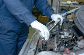 A man servicing dirty engine
